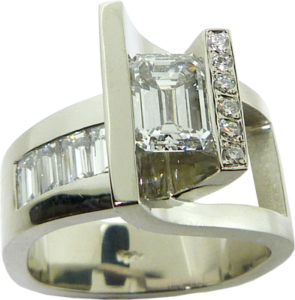 Ring featuring an emerald cut diamond, baguette diamonds, and small round diamond accents