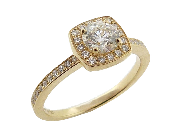 A contemporary halo design surrounds a round center Hearts on Fire diamond. Hidden underneath the diamond sits a small heart. This style is no longer in regular production. Come see our last one in stock! Made with 18 Karat yellow gold, set with a 0.550ct, I, VS2, Hearts on Fire center diamond.