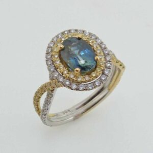 18K white and yellow gold split shank engagement ring, set with an oval brilliant 1.34ct blue-green sapphire. Accented with 46 round brilliant cut natural yellow diamonds, 0.32 carat total weight, SI1 -SI2 and with 50 round brilliant cut diamonds, 0.40 carat total weight, VS2-SI1, G/H.