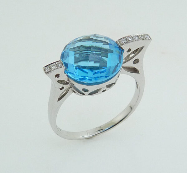 14 karat white gold modern design ring set with a checkerboard cut 5.78ct Swiss Blue Topaz and accented with 8 = 0.048ctw round brilliant cut diamonds.