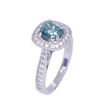 In 18 karat white gold, this vintage inspired halo ring showcases a 1.03 carat cushion cut treated blue diamond. Accented with round brilliant cut diamonds totaling 0.45 carats. The perfect gift for 10th anniversaries, 60th anniversaries, April birthdays or a stunning engagement ring!