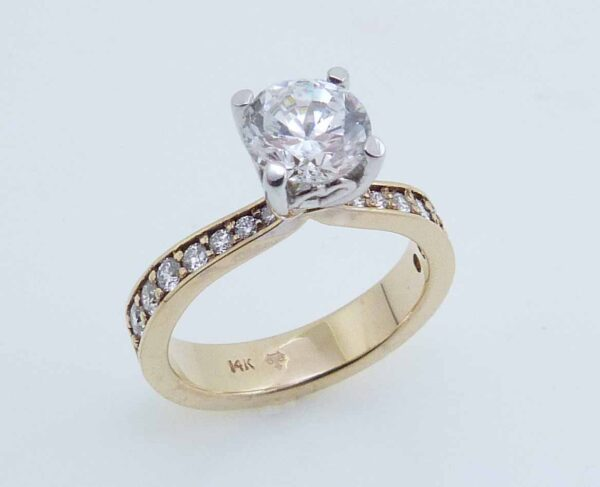 14 karat yellow and white gold solitaire design engagement ring accented by 16 = 0.32ctw excellent cut F/G, VS-SI round brilliant cut diamonds. Priced without a center gemstone. Let us find you the perfect center that fits your tastes and budget!