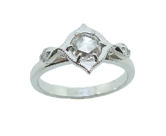 14 karat white gold vintage design halo engagement ring featuring a 0.48ct F/G, SI1 rose cut diamond accented by 2 = 0.054ctw G/H, SI round brilliant cut diamonds. This unique design is a great alternative to a traditional halo ring. This ring is a custom design by David.