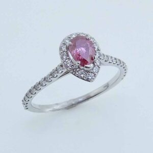 In 14 karat white gold, this halo ring showcases a 0.44 carat pear shaped treated pink diamond set above bezel set peek-a-boo diamonds. Accented with diamonds totaling 0.37 carats. The perfect gift for 10th anniversaries, 60th anniversaries, April birthdays or a stunning engagement ring!