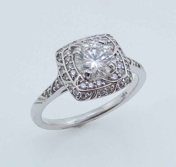 14 karat vintage halo engagement ring featuring a 0.78ct F, SI1, round brilliant cut diamond accented by 0.20ctw round brilliant cut diamonds.