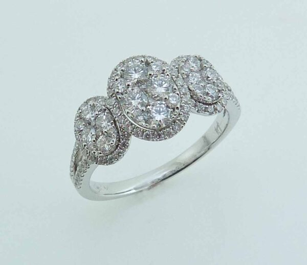 14 karat white split shank cluster three stone halo design engagement ring featuring 112 = 0.99ctw round brilliant cut diamonds. This unique design is a great alternative to a traditional three stone ring. Priced without a center gemstone. Let us find you the perfect center that fits your tastes and budget!