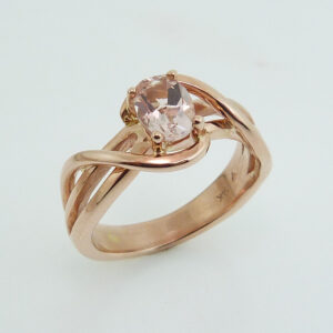 14 karat rose gold ring, showcasing a 0.72 carat oval shaped Morganite. Created by our jeweler and owner, David Blitt as part of our Studio Tzela line. A unique piece that can be used as an engagement ring or a fashion ring.