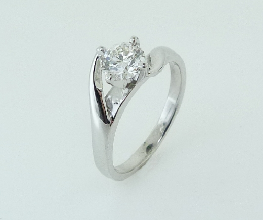 19 karat white gold and platinum solitaire engagement ring featuring a 0.623ct I, VS2 round brilliant cut diamond by Hearts on Fire. A matching wedding band is available.