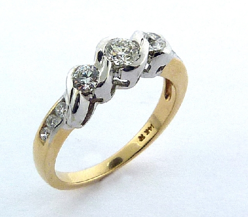 14K yellow and white gold three stone engagement ring by Studio Tzela. Semi-bezel and pave set with ideal cut, round brilliant cut Hearts On Fire diamonds featuring a 0.244ct H, SI1 centre and accented on the sides and band with 0.273 carat total weight Hearts On Fire diamonds, SI1-SI2, G/H.