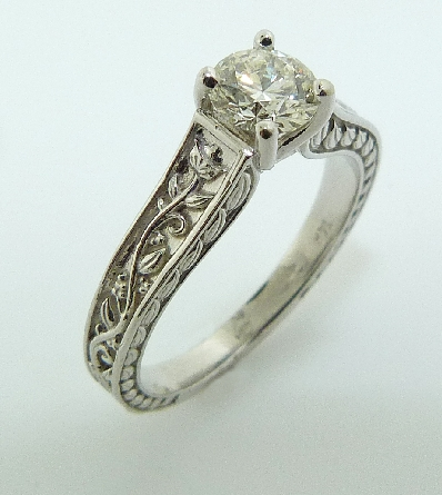 14 karat white gold custom solitaire engagement ring featuring a 0.448ct, E, VS1 round brilliant cut diamond by Hearts on Fire. This unique ring also features beautiful engraving on the band. This ring is a custom design by David.