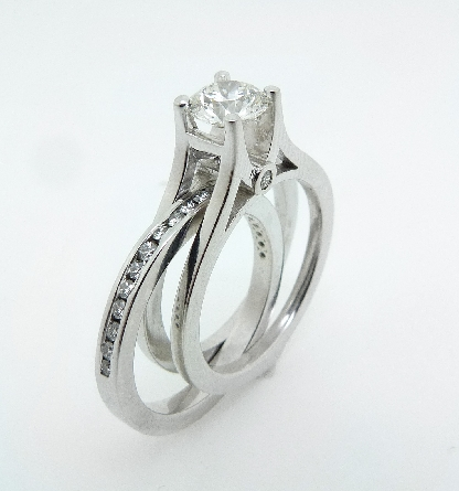 14 karat white gold custom wedding set featuring an engagement ring set with a 0.712ct J, VS2 round brilliant cut diamond by Hearts on Fire accented by 2 = 0.04ctw round brilliant cut diamonds. The wedding band is set with 0.77ctw G/H, VS2/SI1 round brilliant cut diamonds. This wedding set is a custom design by David.