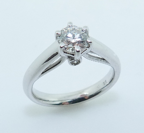14 karat white gold custom solitaire engagement ring featuring a 0.742ct, G, SI1 round brilliant cut diamond by Hearts on Fire accented by 2 = 0.04ctw round brilliant cut diamonds. This ring is a custom design by David.