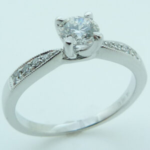 14 karat white gold engagement ring set with a 0.438ct G, SI1 round brilliant cut diamond by Hearts on Fire accented by 8 = 0.09ctw round brilliant cut diamonds. This stunning ring features milgrain engraving.