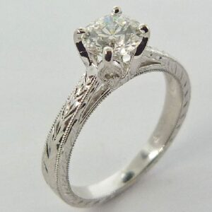 14 karat white gold solitaire engagement ring featuring a 0.780ct, G, SI1 round brilliant cut diamond by Hearts on Fire accented by 0.027ctw round brilliant cut diamonds.