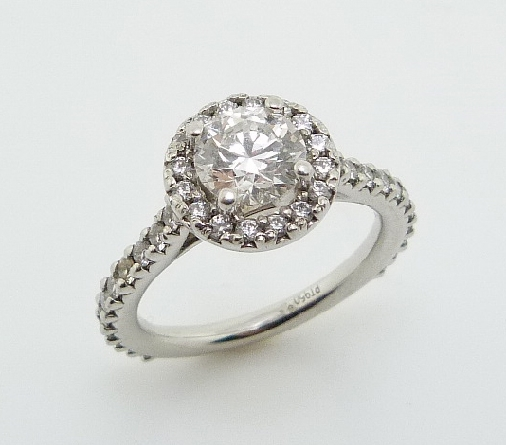 Platinum halo engagement ring featuring a 0.786ct, F, SI1 round brilliant cut diamond by Hearts on Fire accented by 38 = 0.45ctw round brilliant cut diamonds.