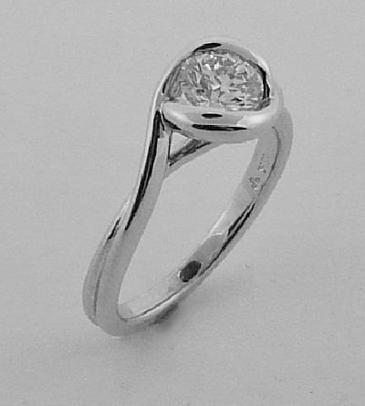14 karat white gold twist design solitaire engagement ring set with a 0.646ct I, VI1 round brilliant cut diamond by Hearts on Fire.
