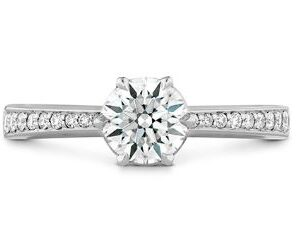 Signature 4 prong solitaire engagement ring with diamonds on the band by Hearts on Fire is available in 18 karat yellow and white gold as well as platinum