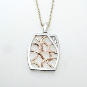 14 karat white and rose gold custom pendant set with a 3= 0.093ct H, VS-SI1, Hearts on Fire diamonds. This stunning pendant is a custom design by David.