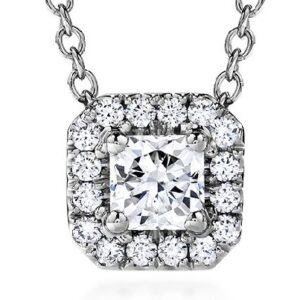18K White gold Transcend Single Halo Dream Pendant by Hearts On Fire set with a 3.8mm, G/H, VS- S1, Dream diamond and accented with twelve G/H, VS-SI, 1.4 mm ideal cut, round brilliant cut diamonds by Hearts On Fire, totaling 0.42-0.52ctw, with a 18K white gold cable chain featuring an extension.
