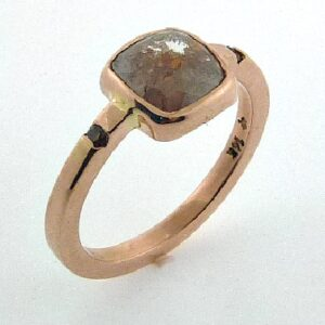 14K Rose gold ring bezel set with a 1.49ct rose cut, cushion cut, rustic diamond and accented on the band with 2 channel set natural brown coloured, round brilliant cut diamonds, 0.034cttw, SI.