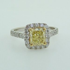 14 karat white halo engagement ring featuring a 1.23ct natural fancy yellow cut cornered modified brilliant diamond and accented by 0.56ctw round brilliant cut diamonds
