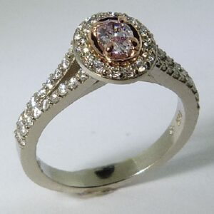 14 karat white and rose halo engagement ring featuring a 0.253ct natural pink round oval cut diamond and accented by 52 = 0.37ctw excellent cut, F/G, VS/SI round brilliant cut diamonds