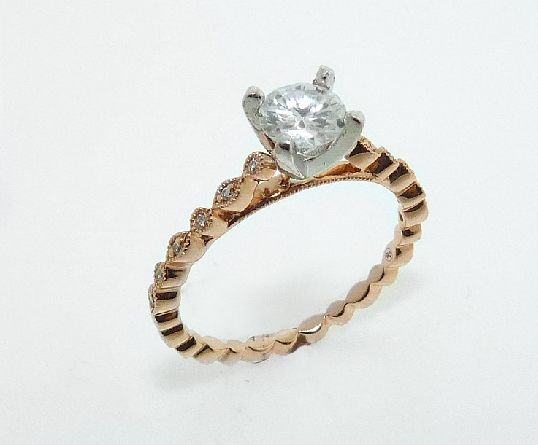 14 karat white and rose vintage solitaire design engagement ring accented by 12 = 0.04ctw round brilliant cut diamonds. This unique design has stunning milgrain engraving and is a great alternative to a traditional solitaire ring.