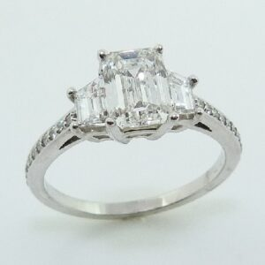 14 karat three stone engagement ring featuring a 1.24ct G, VVS2 Emerald cut diamond with 2 = 0.61ctw F/G, VS trapezoid cut diamonds and accented by 0.118ctw of round brilliant cut diamonds.