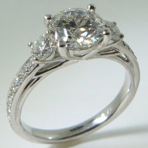 18 karat white three stone engagement ring accented by 2 = 0.39ctw G/H, SI1 round brilliant cut diamonds and 18 = 0.163ctw G/H, SI1 round brilliant cut diamonds.