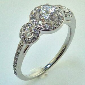 14 karat white three stone halo engagement ring featuring 2 = 0.09ctw round brilliant cut diamonds and 50 = 0.253ctw that go halfway down the band.