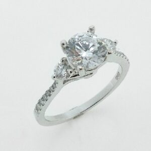 18 karat white three stone engagement ring accented by 0.40ctw round brilliant cut diamonds.