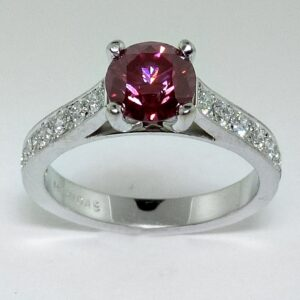 14K White gold ring claw set in the centre with 1.26ct treated pink diamond, GIA graded. Accented on the band with 14 pave set, round brilliant cut diamonds totaling 0.48 carats, G/H, SI1.