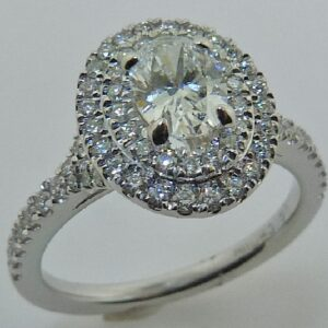 19 karat white double halo engagement ring featuring a 0.56ct E, VVS2 oval cut diamond accented by 0.50ctw round brilliant cut diamonds.