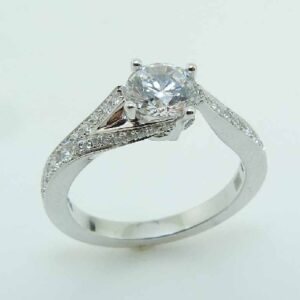 14K White gold Frederic Sage engagement ring with 0.75ct round CZ and a split band that wraps around underneath the centre featuring 2 pave set round brilliant cut diamonds, 0.05cttw, and an additional 38 pave set diamonds, 0.25cttw, G/H, VS-SI. Available in 14K gold, 18K gold, or platinum. This ring can be made in any combination of white, pink or yellow gold and can be customized to accommodate different size and shape diamonds, by special order. Priced without a center gemstone. Let us find you the perfect center that fits your tastes and budget!