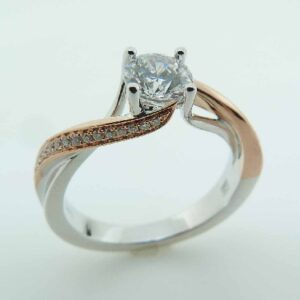 14K White gold engagement ring with a rose gold accents by Frederic Sage set with a 0.50ct round CZ and pave set on the band with 32 round brilliant cut diamonds, 0.11cttw, G/H, VS-SI. Available in 14K gold, 18K gold, or platinum. This ring can be made in any combination of white, pink or yellow gold and can be customized to accommodate different size and shape diamonds, by special order. Priced without a center gemstone. Let us find you the perfect center that fits your tastes and budget!