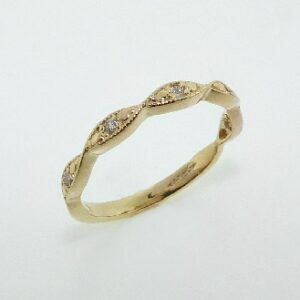14 karat yellow gold band set with 5 = 0.07ctw , G/H, SI round brilliant cut diamonds. This ring features milgrain engraving and looks stunning by itself or as part of a stack.
