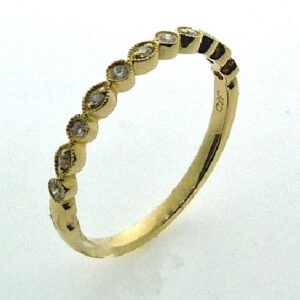 14 karat yellow gold band set with 11 = 0.09ctw , G/H, SI round brilliant cut diamonds. This ring features milgrain engraving and looks stunning by itself or as part of a stack.