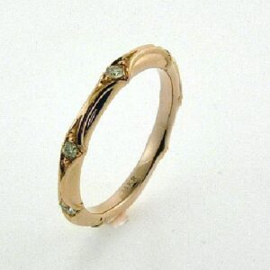 14 karat rose gold band set with 7 = 0.144ctw H/I, SI2-I1 round brilliant cut diamonds.