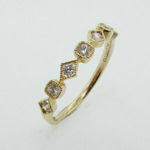 14 karat yellow gold band set with 7 = 0.23ctw , G/H, SI round brilliant cut diamonds.