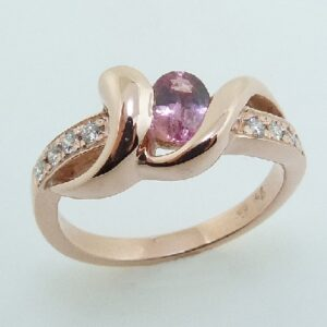 14 karat rose gold open design ring featuring an oval 0.46ct Padparadscha sapphire and accented with 0.112ctw of round brilliant cut diamonds.