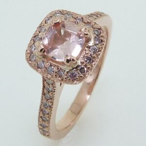 14 karat rose gold ring featuring a stunning Padparadscha sapphire accented with natural fancy pink diamonds in the halo and on the shoulders.