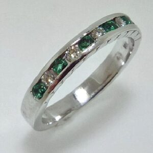 14 karat white gold band channel set with 6 = 0.22ctw emeralds and 5 = .14ctw excellent cut, F/G, VS2-SI1, round brilliant cut diamonds.