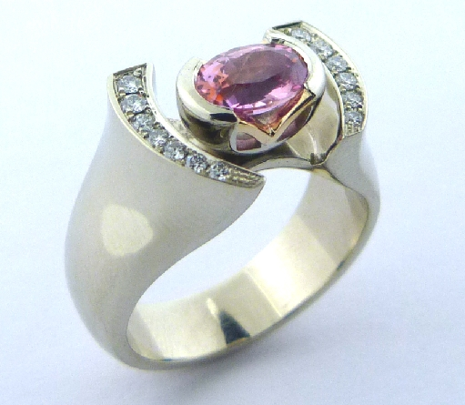 14K white gold custom ring by Studio Tzela with a semi-bezel set 1.10ct oval Padparadscha pink sapphire and 13 pave set diamonds, 0.14cttw.