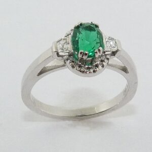 14 karat white gold ring set with a 0.76ct emerald, 12 = 0.045ctw F/G, SI, round brilliant cut diamonds and 2 = 16ctw F/G, VS1-2, round brilliant cut diamonds