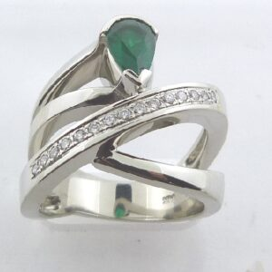 14 karat white gold ring set with a 0.60ct pear shaped emerald and accented by 15 = 0.082ctw, G/H, SI, round brilliant cut diamonds