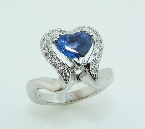 14K white gold custom ring by Studio Tzela claw set with a 1.63ct heart shape blue sapphire and accented with 18 pave set diamonds, 0.131cttw.