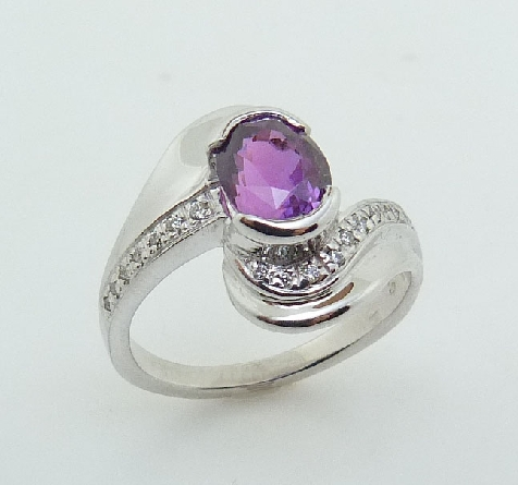 14K white gold custom bypass style ring by Studio Tzela semi bezel set with a natural purple oval cut sapphire, 1.74ct and accented with 17 diamonds, 0.063cttw.