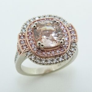 14K white and rose gold double halo custom lady's ring by Studio Tzela showcasing a 2.30ct peach coloured sapphire and 42 natural fancy pink diamonds, 0.29cttw and 37 excellent cut, round brilliant cut diamonds, 0.317cttw.