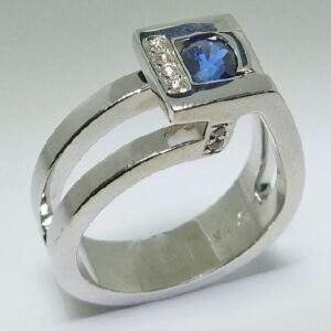 14K white gold lady's ring custom designed by Studio Tzela featuring a bezel set 0.655ct blue sapphire and 8 pave set accent diamonds on the bezel and the profile, 0.058cttw.