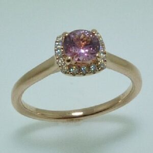 14 karat rose gold ring featuring a 0.517ct pink sapphire accented with a halo of 0.11ctw of round brilliant cut diamonds.
